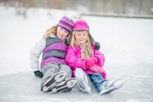 Little Girls Sitting on a Frozen Lake